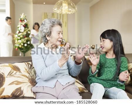 grandma and granddaughter playing at home - stock photo