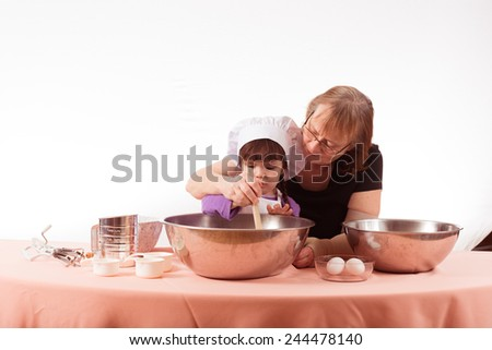 Grandma and granddaughter stirring together - stock photo
