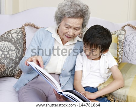 grandma and grandson reading a book together. - stock photo