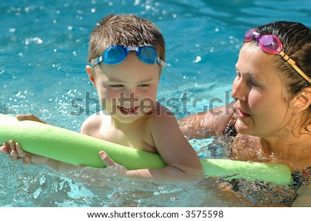 Grandma and her little grandson playing in the swimming pool - stock photo