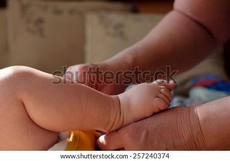 grandma dresses up a baby - stock photo
