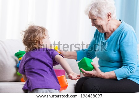 Grandma playing with her grandchild on couch