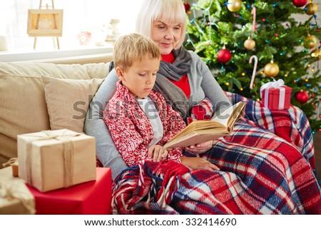 Grandma reading Christmas story to her grandson - stock photo