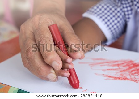 Grandma's hand holding child hand drawing with crayon,soft color filter - stock photo