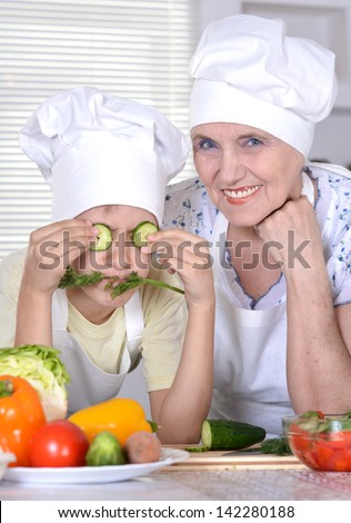 grandma with her grandson is preparing dinner for the whole family - stock photo