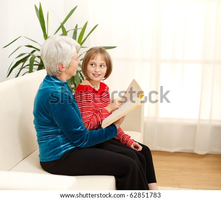 Grandmama sitting on sofa with grandchild and reading book - stock photo