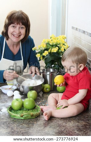 Grandmother and baby boy baking in the kitchen - stock photo