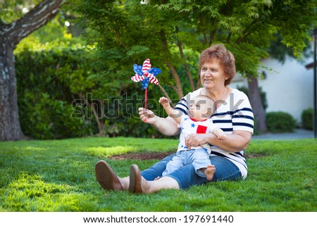 Grandmother and baby boy playing with a pinwheel on a a green lawn