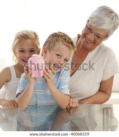 Grandmother and children saving money in a piggybank - stock photo
