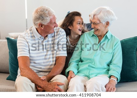Grandmother and grand father with their granddaughter sitting on sofa in living room - stock photo