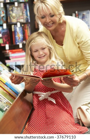 Grandmother and grandaughter in bookshop - stock photo