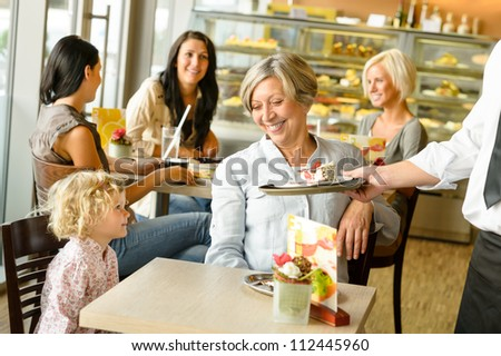 Grandmother and grandchild waiting cake order cafe dessert waiter plate - stock photo