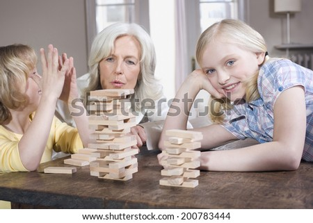 Grandmother and grandchildren playing with engage together - stock photo