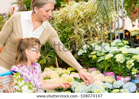 Grandmother and granddaughter buying flowers at garden centre