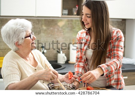 Grandmother and granddaughter cooking in the kitchen. - stock photo