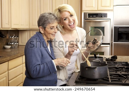 Grandmother and granddaughter cooking in the kitchen together and having fun - stock photo