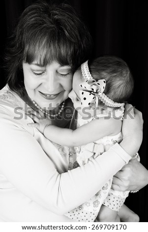 Grandmother and granddaughter cuddling against brown background - stock photo