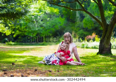 Grandmother and granddaughter enjoying picnic in a park. Grandma playing with little toddler girl in a sunny autumn forest. Summer outdoor fun in the garden. Grandparents and kids on a meadow. - stock photo