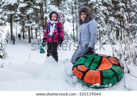 Grandmother and granddaughter going for a walk, riding on an inflatable tube from hill in the winter forest - stock photo