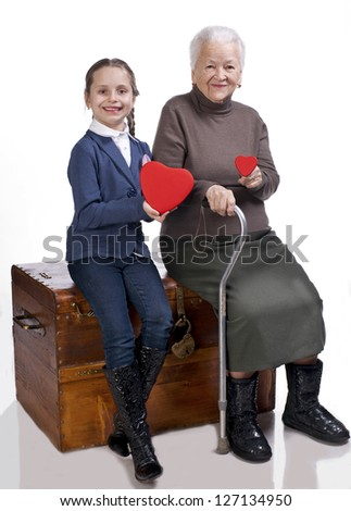 Grandmother and granddaughter holding hearts on a white background - stock photo