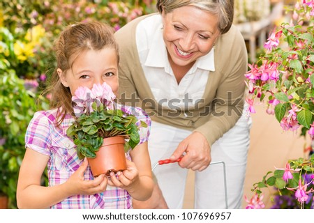 Grandmother and granddaughter holding purple potted cyclamen at garden center