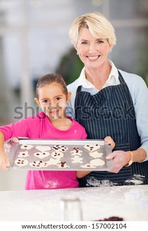 grandmother and granddaughter holding tray of homemade cookies to be baked - stock photo