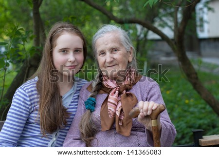 Grandmother and granddaughter laughing in the park in summer