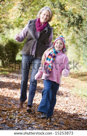 Grandmother and granddaughter playing in autumn woods - stock photo