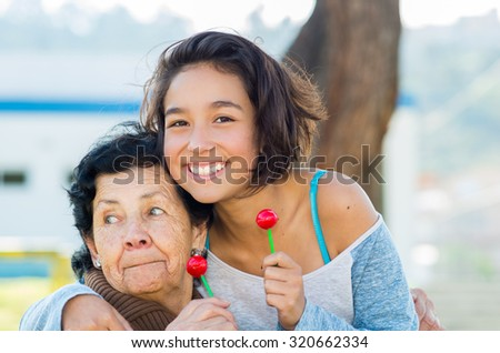 Grandmother and granddaughter posing happily together holding lollipops smiling. - stock photo