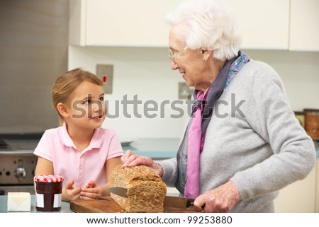 Grandmother and granddaughter preparing food in kitchen - stock photo