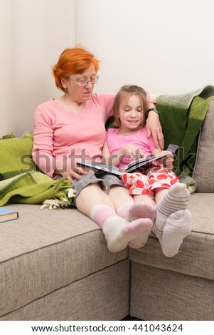 grandmother and granddaughter read stories together in room on sofa - stock photo