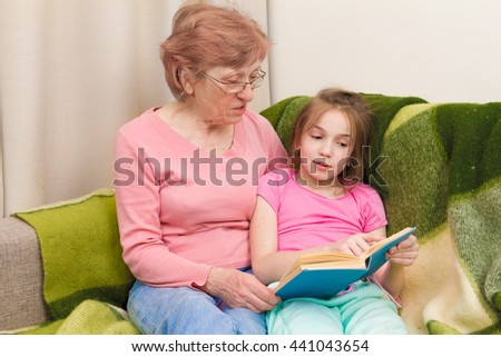 grandmother and granddaughter reading together, they sit together, hold book, read and smile - stock photo