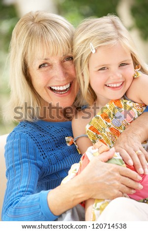 Grandmother And Granddaughter Relaxing On Sofa Together - stock photo