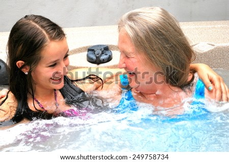 Grandmother and granddaughter relaxing together in the hot tub. - stock photo