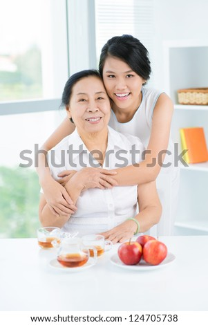 Grandmother and granddaughter sitting and embracing