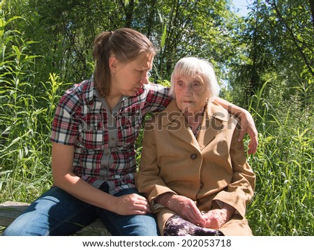 Grandmother and granddaughter sitting on a bench on a background of grass - stock photo