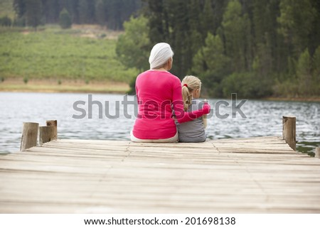 Grandmother and granddaughter sitting on a jetty - stock photo