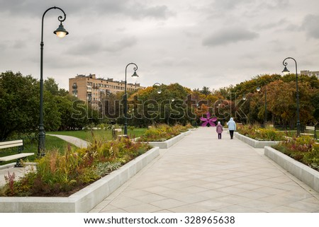 Grandmother and granddaughter walk in the park in autumn - stock photo