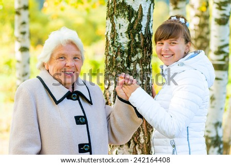 grandmother and granddaughter walking in the autumn park - stock photo