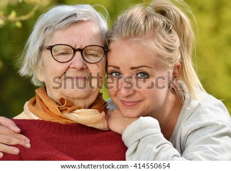 Grandmother and granddaughter. Young woman carefully takes care of an older woman. MANY OTHER PHOTOS FROM THIS SERIES IN MY PORTFOLIO.