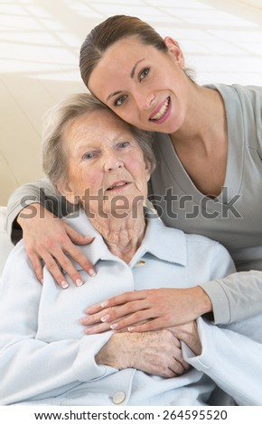 Grandmother and granddaughter. Young woman takes care of an elderly woman. - stock photo