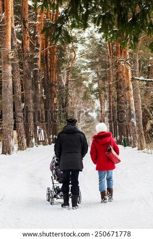 Grandmother and grandfather are walking with their baby-grandson in winter - stock photo