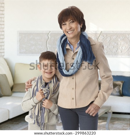 Grandmother and grandson embracing at home, smiling happy, looking at camera. - stock photo