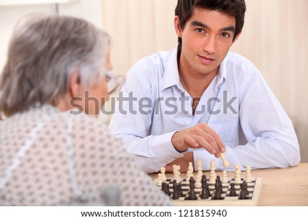 Grandmother and grandson playing chess