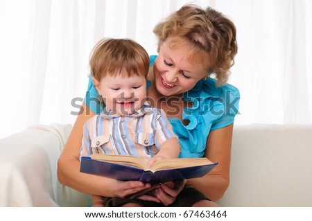 Grandmother and grandson reading a book together. Symbol of the family. - stock photo