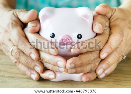 Grandmother and her daughter covering piggy bank together, metaphoric for hope, retirement, pension and life insurance. image focus at piggy bank face - stock photo