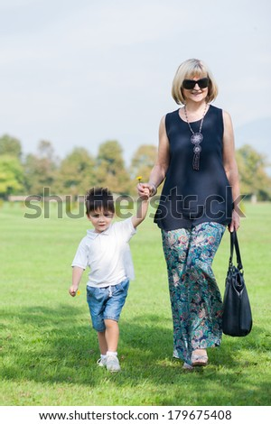 Grandmother and his grandson are walking in the park. - stock photo