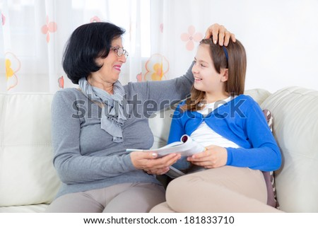 Grandmother and little girl reading magazine happy together at home - stock photo