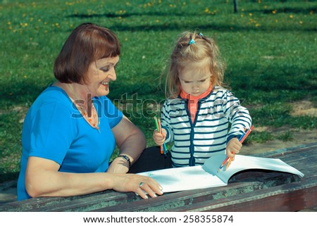 Grandmother and little granddaughter paint outdoors - stock photo