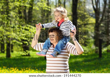 Grandmother and little granddaughter playing on the meadow of yellow dandelions. Grandmother carries his granddaughter on his shoulders - stock photo